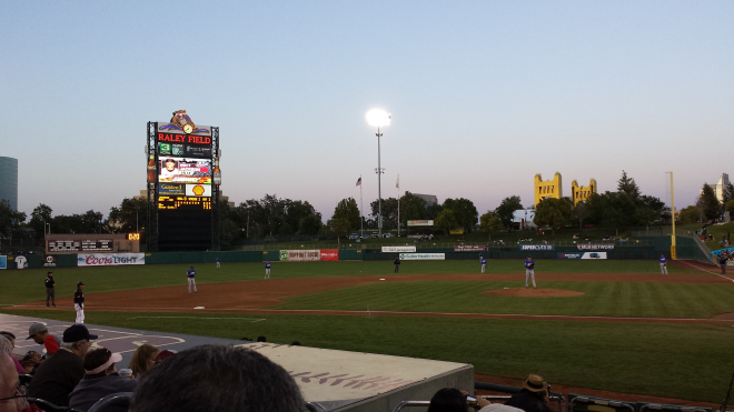 The sun sets at River Cats Ballpark in West Sacramento. The golden Tower Bridge is in the middle distance.
